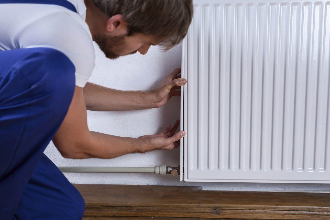 Homme qui fixe un radiateur